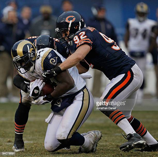Jamar Williams and Hunter Hillenmeyer of the Chicago Bears bring down Randy McMichael of the St Louis Rams at Soldier Field on December 6 2009 in...