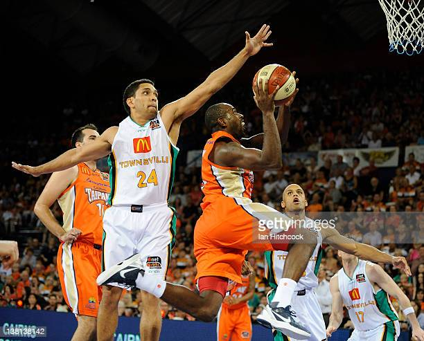Jamar Wilson of the Taipans makes a layup past Michael Cedar of the Crocodiles during the round 18 NBL match between the Cairns Taipans and the...