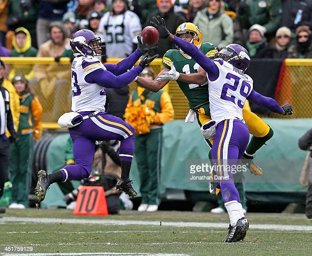Jamarca Sanford of the Minnesota Vikings breaks up a pass intended for Jarrett Boykin of the Green Bay Packers as Xavier Rhodes also defends at...