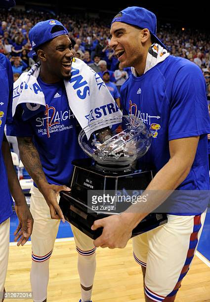 Jamari Traylor and Landen Lucas of the Kansas Jayhawks hold the Big 12 Conference Championship trophy after they defeated Texas Tech Red Raiders...