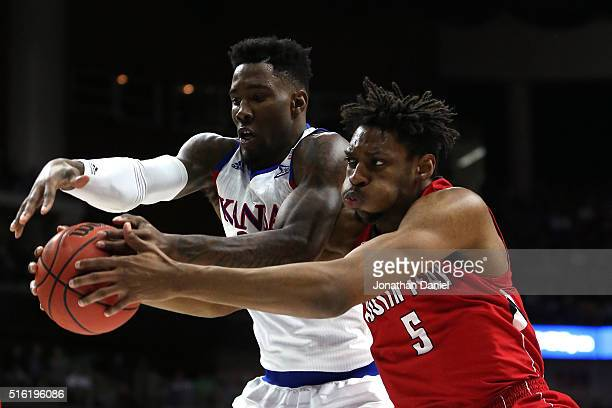 Jamari Traylor of the Kansas Jayhawks and Chris Horton of the Austin Peay Governors go for a rebound in the first half during the first round of the...
