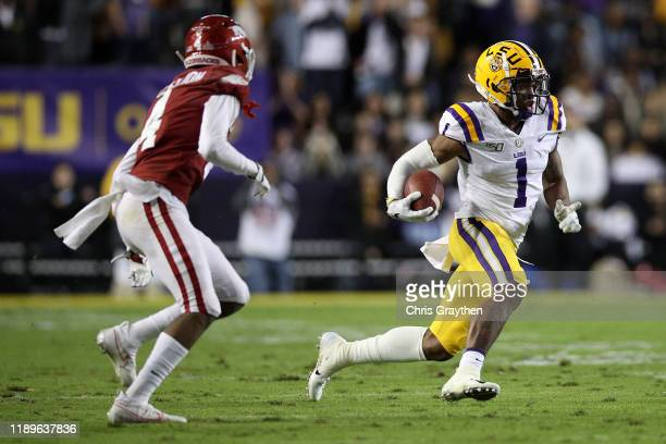 Ja'Marr Chase of the LSU Tigers avoids a tackle by Jarques McClellion of the Arkansas Razorbacksat Tiger Stadium on November 23 2019 in Baton Rouge...