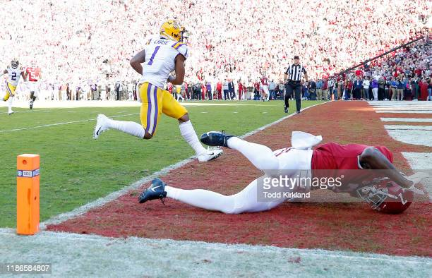 Ja'Marr Chase of the LSU Tigers scores a 33yard receiving touchdown during the first quarter as Trevon Diggs of the Alabama Crimson Tide falls down...