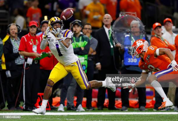 Ja'Marr Chase of the LSU Tigers scores a touchdown as AJ Terrell of the Clemson Tigers defends in the College Football Playoff National Championship...