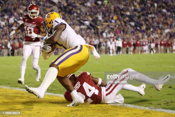 Ja'Marr Chase of the LSU Tigers scores a touchdown over LaDarrius Bishop of the Arkansas Razorbacks at Tiger Stadium on November 23 2019 in Baton...