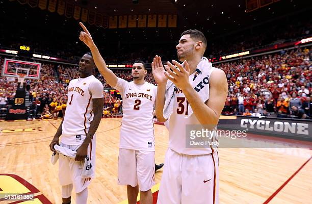 Jameel McKay Abdel Nader and Georges Niang of the Iowa State Cyclones celebrate with fans at mid court on senior night after defeating the Oklahoma...