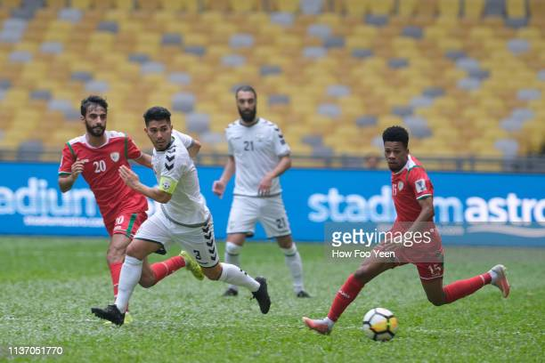 Jameel Saleem Jameel Al Yahmadi of Oman and Hassan Amin of Afghanistan in action during the Airmarine Cup match between Oman and Afghanistan at Bukit...