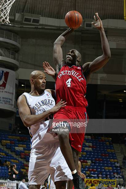 Jameel Watkins of the Fayetteville Patriots dunks over Darrell Johns of the Roanoke Dazzle during the NBDL Playoffs at the Crown Coliseum on March...