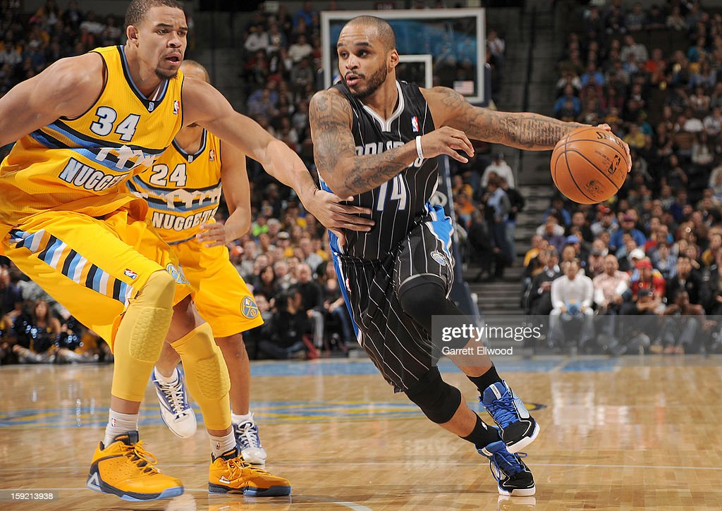 Jameer Nelson #14 of the Orlando Magic drives against JaVale McGee #34 of the Denver Nuggets during the game between the Orlando Magic and the Denver Nuggets on January 9, 2013 at the Pepsi Center in Denver, Colorado.