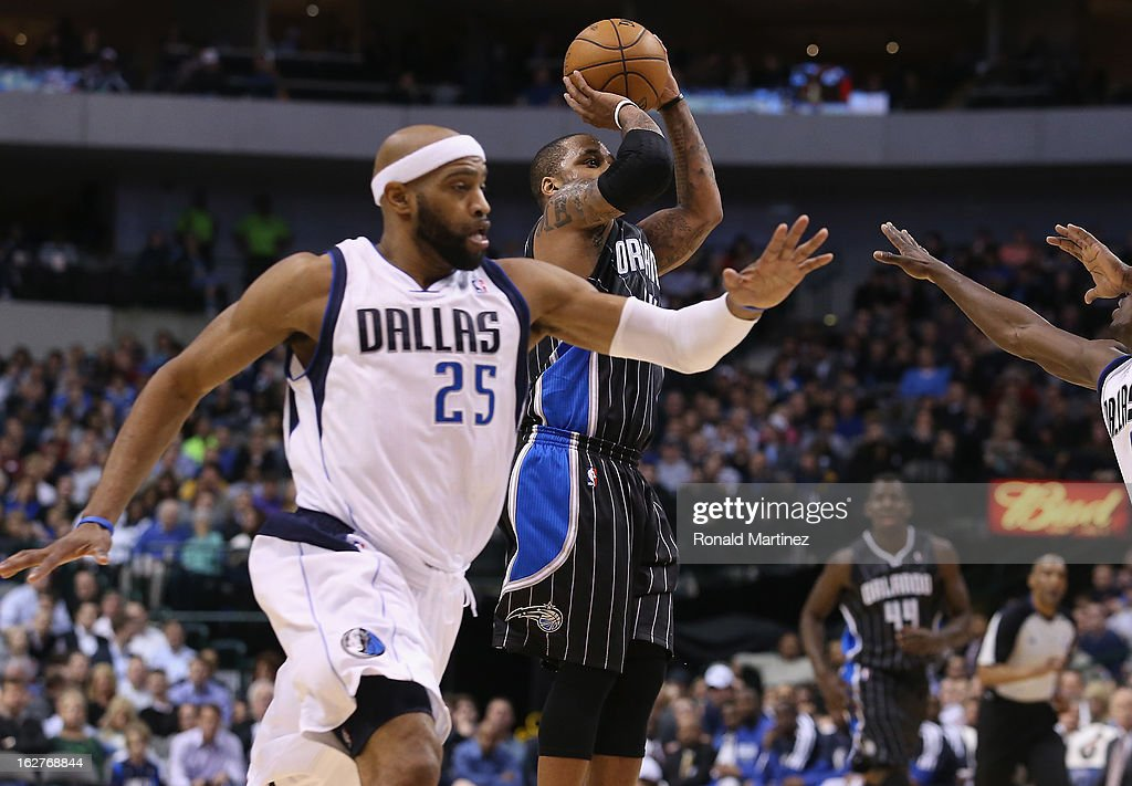 Jameer Nelson #14 of the Orlando Magic takes a shot against Vince Carter #25 of the Dallas Mavericks at American Airlines Center on February 20, 2013 in Dallas, Texas.