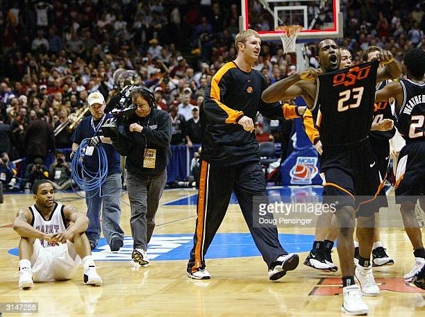 Jameer Nelson of the St Joseph's Hawks sits dejected as Ivan McFarlin of the Oklahoma State Cowboys celebrates after winning 6462 in their fourth...