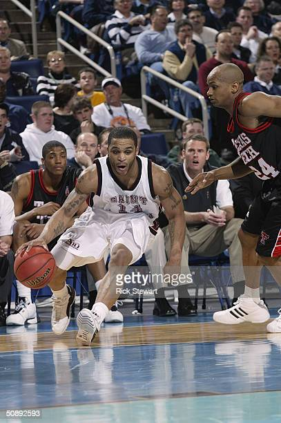Jameer Nelson of the St. Joseph's University Hawks is defended by Ronald Ross of the Texas Tech University Red Raiders during the second round of the...