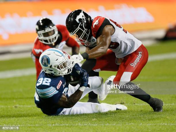 Jameer Thurman of the Calgary Stampeders makes a tackle on James Wilder Jr #32 of the Toronto Argonauts during a CFL game at BMO Field on August 3...