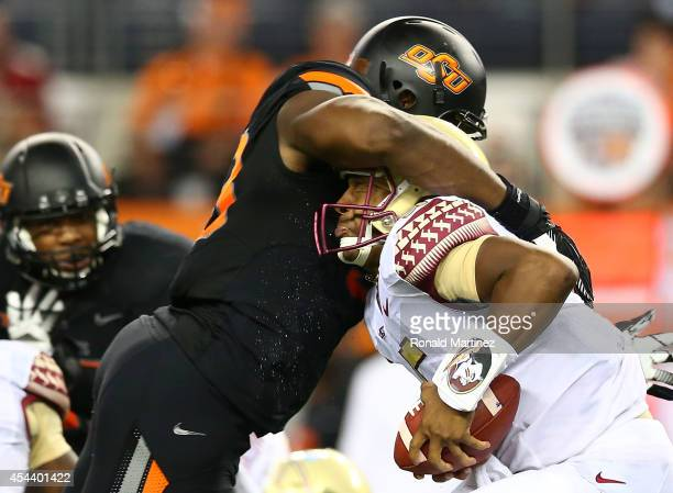 Jameis Winston of the Florida State Seminoles is sacked by Emmanuel Ogbah of the Oklahoma State Cowboys in the first half of the Advocare Cowboys...