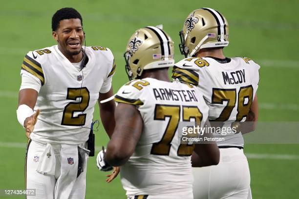 Jameis Winston of the New Orleans Saints celebrates with teammates Terron Armstead and Erik McCoy after they scored a touchdown against the Las Vegas...