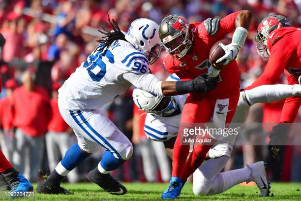 Jameis Winston of the Tampa Bay Buccaneers breaks a tackle by Denico Autry of the Indianapolis Colts during the second quarter of a football game at...