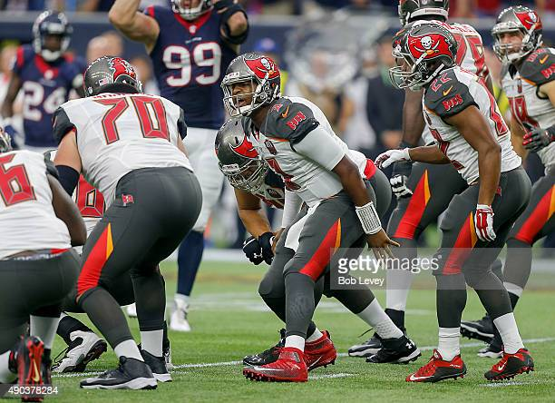 Jameis Winston of the Tampa Bay Buccaneers changes the play at the line as Logan Mankins listens in at NRG Stadium on September 27, 2015 in Houston,...