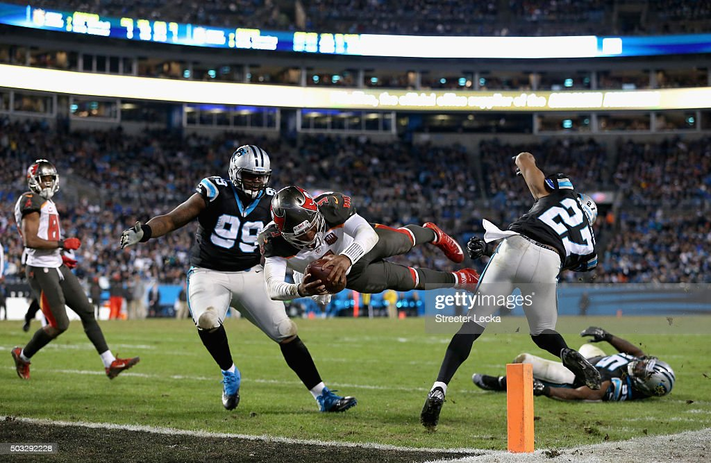 Jameis Winston #3 of the Tampa Bay Buccaneers dives for a touchdown against teammates Kawann Short #99 and Robert McClain #27 of the Carolina Panthers during their game at Bank of America Stadium on January 3, 2016 in Charlotte, North Carolina.