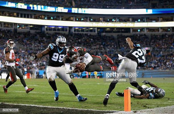 Jameis Winston of the Tampa Bay Buccaneers dives for a touchdown against teammates Kawann Short and Robert McClain of the Carolina Panthers during...