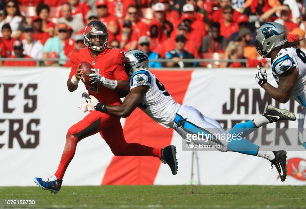 Jameis Winston of the Tampa Bay Buccaneers gets sacked by Efe Obada of the Carolina Panthers for an eight yard loss during the second quarter at...