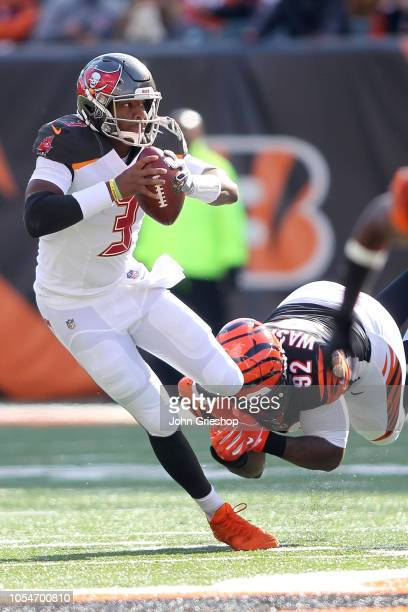 Jameis Winston of the Tampa Bay Buccaneers is tackled by Adolphus Washington of the Cincinnati Bengals during the third quarter at Paul Brown Stadium...
