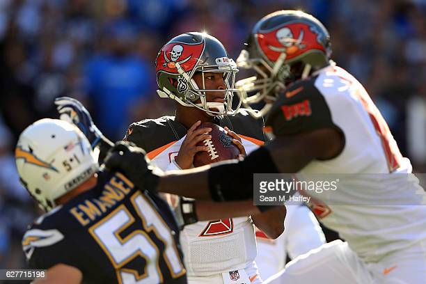 Jameis Winston of the Tampa Bay Buccaneers looks to pass under pressure from Kyle Emanuel of the San Diego Chargers during the second half of a game...