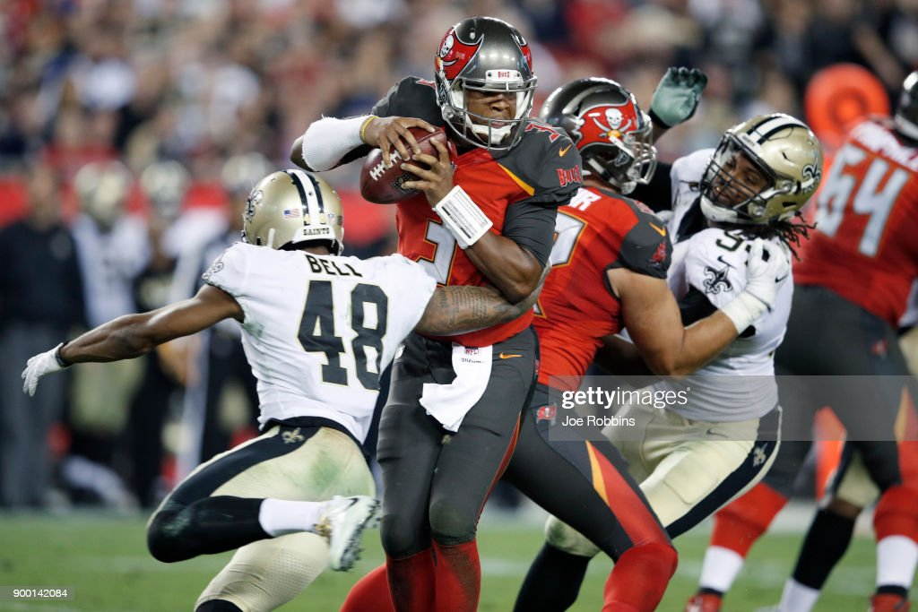 Jameis Winston #3 of the Tampa Bay Buccaneers tries to avoid being sacked by Vonn Bell #48 of the New Orleans Saints in the third quarter of a game at Raymond James Stadium on December 31, 2017 in Tampa, Florida. The Buccaneers won 31-24.