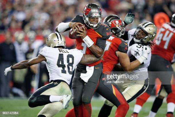 Jameis Winston of the Tampa Bay Buccaneers tries to avoid being sacked by Vonn Bell of the New Orleans Saints in the third quarter of a game at...