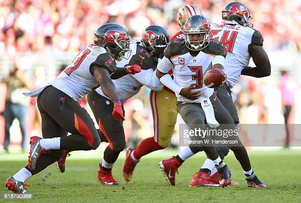 Jameis Winston of the Tampa Bay Buccaneers turns to hand the ball off to running back Peyton Barber against the San Francisco 49ers during the fourth...