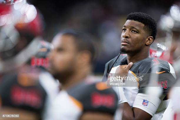 Jameis Winston of the Tampa Bay Buccaneers watches a replay on the screen from the sidelines after being hurt in the first half of a game against the...