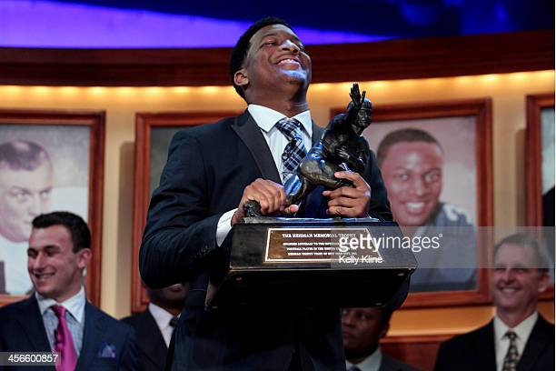 Jameis Winston quarterback of the Florida State Seminoles hoist the trophy after being named the 79th Heisman Memorial Trophy Award winner during the...