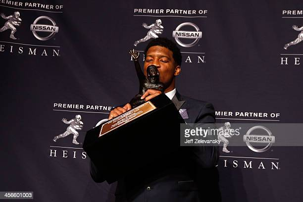 Jameis Winston quarterback of the Florida State Seminoles kisses the trophy during a press conference after the 2013 Heisman Trophy Presentation at...