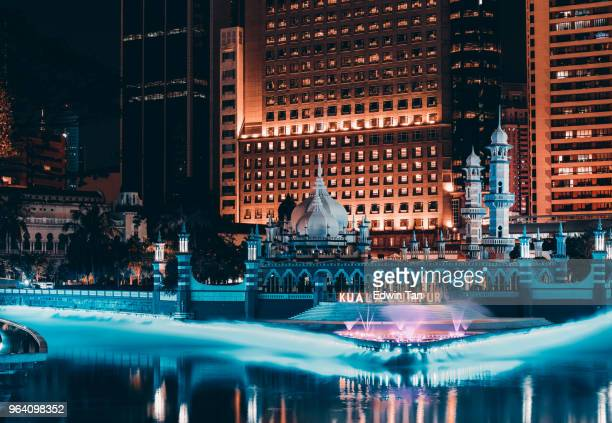 jamek mosque in the heart of kuala lumpur in malaysia at night in front of river of life - emerging markets stock photos and pictures