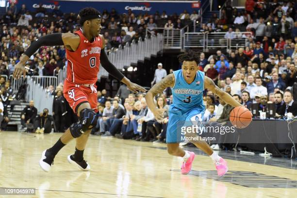 James Akinjo of the Georgetown Hoyas dribbles around Sedee Keita of the St John's Red Storm a college basketball game at the Capital One Arena on...