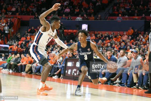 James Akinjo of the Georgetown Hoyas dribbles around Tevian Jones of the Illinois Fighting Illini during a college basketball game at the State Farm...