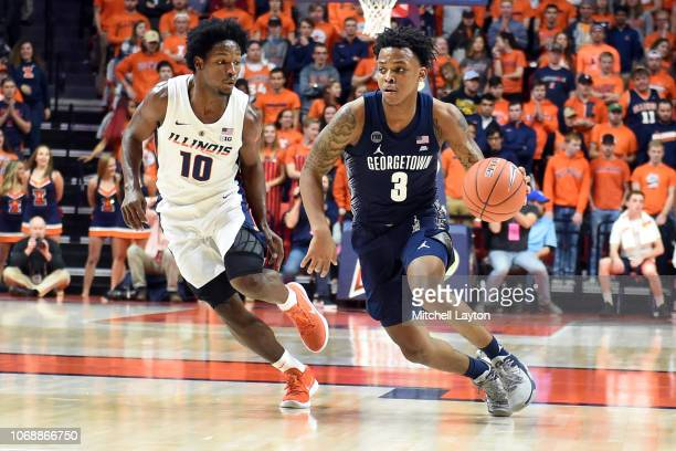 James Akinjo of the Georgetown Hoyas dribbles by Andres Feliz of the Illinois Fighting Illini during a college basketball game at the State Farm...
