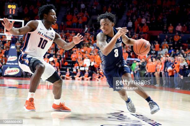 James Akinjo of the Georgetown Hoyas dribbles round Andres Feliz of the Illinois Fighting Illini during a college basketball game at the State Farm...