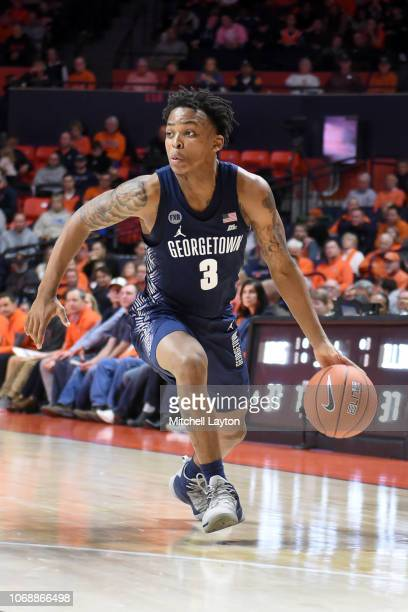 James Akinjo of the Georgetown Hoyas dribbles the ball during a college basketball game against the Illinois Fighting Illini at the State Farm Center...