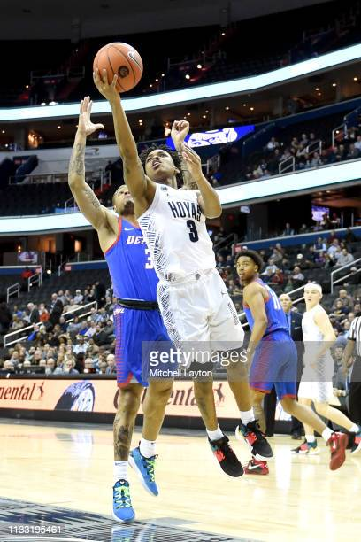 James Akinjo of the Georgetown Hoyas drives to the basket by Devin Gage of the DePaul Blue Demons during a college basketball game at the Capital One...