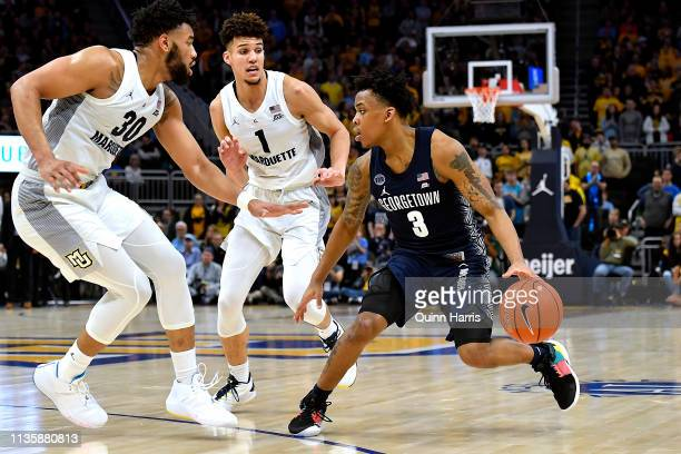 James Akinjo of the Georgetown Hoyas handles the ball against Ed Morrow and Brendan Bailey of the Marquette Golden Eagles at Fiserv Forum on March 09...