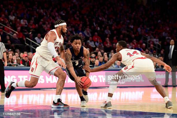 James Akinjo of the Georgetown Hoyas is defended by Marvin Clark II and Mustapha Heron of the St John's Red Storm at Madison Square Garden on January...