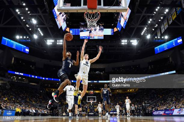 James Akinjo of the Georgetown Hoyas shoots a lay up against Sam Hauser of the Marquette Golden Eagles at Fiserv Forum on March 09 2019 in Milwaukee...