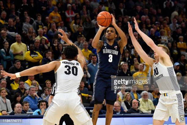 James Akinjo of the Georgetown Hoyas shoots a three point basket against Ed Morrow and Sam Hauser of the Marquette Golden Eagles in the second half...