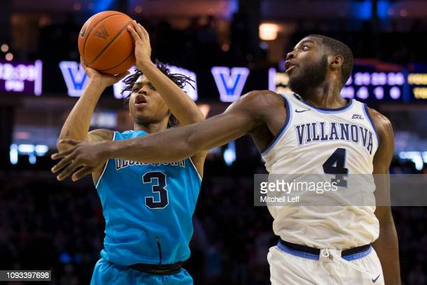 James Akinjo of the Georgetown Hoyas shoots the ball against Eric Paschall of the Villanova Wildcats in the first half at the Wells Fargo Center on...
