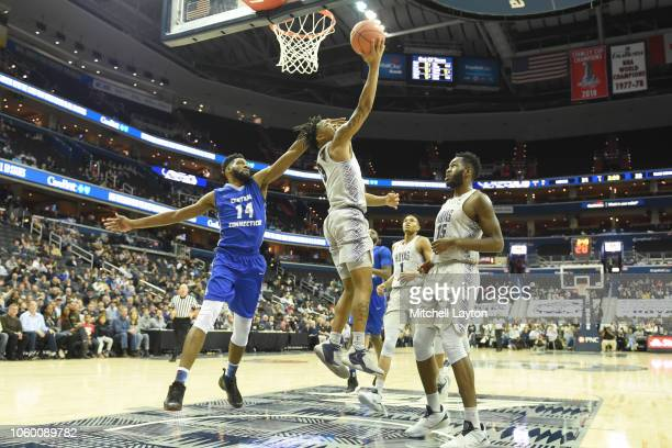 James Akinjo of the Georgetown Hoyas takes a shot over Deion Bute of the Central Connecticut State Blue Devils during a college basketball game at...