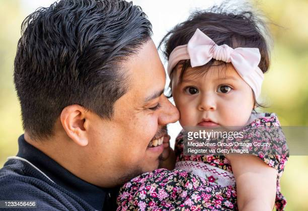 James Alvarez, left, plays with his 10-month-old daughter Adalyn Rose Alvarez-Aguilar at Stoddard Park in Anaheim on Sunday, June 13, 2021. Last...