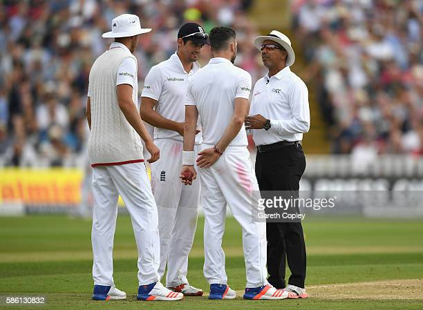 James Anderson of England alongside England captain Alastair Cook is spoken to by umpire Joel Wilson after running on the pitch for 3rd time during...