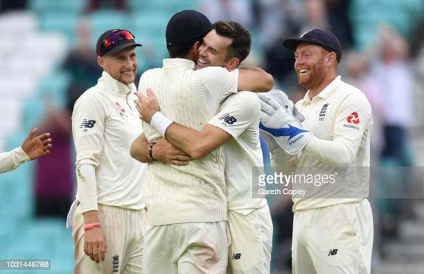 James Anderson of England celebrates with Alastair Cook after taking the final wicket of Mohammed Shami to become the record test wicket taker for a...