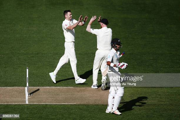 James Anderson of England celebrates with teammate for the wicket of Jeet Raval of New Zealand during day one of the First Test match between New...