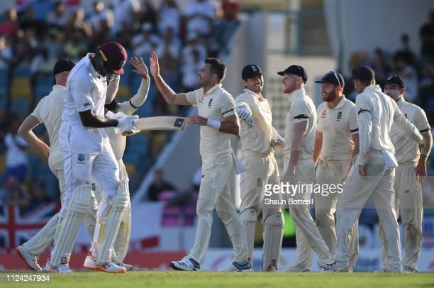 James Anderson of England celebrates with teammates after taking the wicket of West Indies captain Jason Holder during Day One of the First Test...